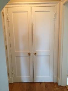 Symmetrical double doors open to reveal a single doorway and a hidden cupboard